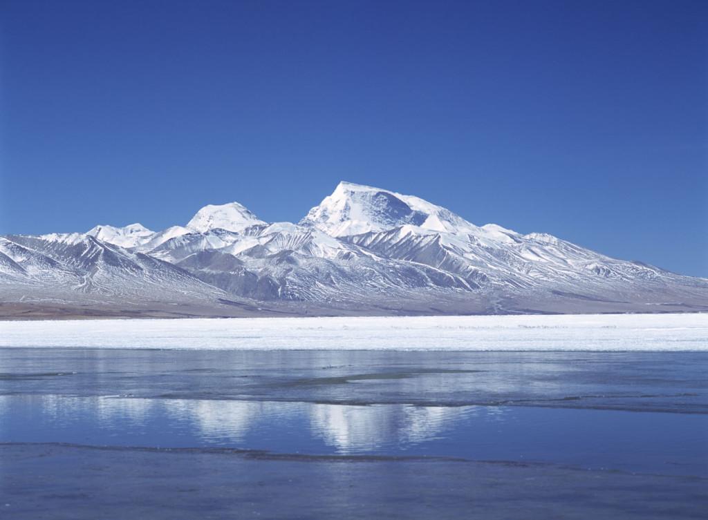Looking across a partially frozen Lake Manasarovar to Mt Memo Nani, Tibet. © Ian Cumming / Tibet Images
